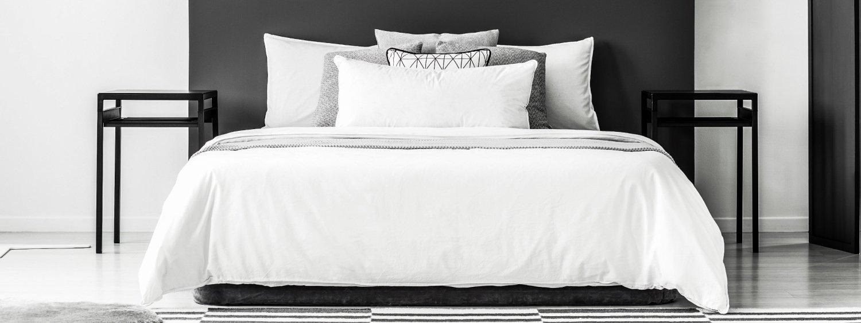 photo prise de face d'un lit avec des tables de chevets sur chaque coté, design moderne