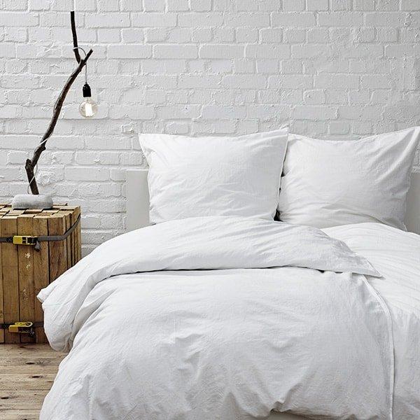 Photo de face de la moitié d'un lit avec coussin joliment disposés